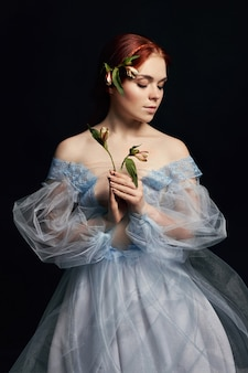 Portret van een vrouw met een middeleeuwse bloem in haar handen op de omslag van het boek. perfecte natuurlijke schoonheid van een meisje met lang haar