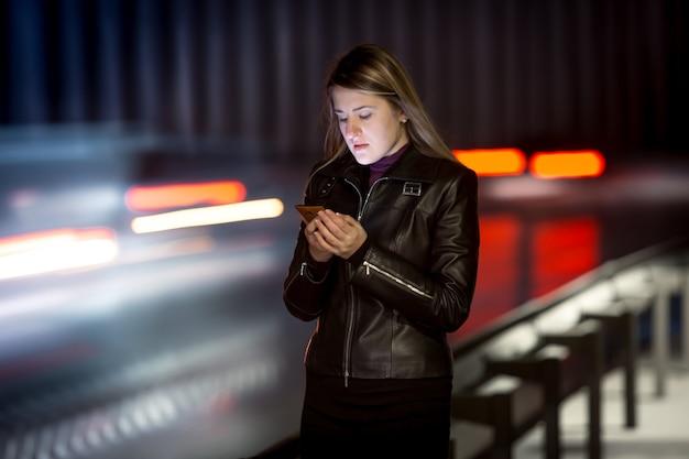 Portret van een vrouw met een mobiele telefoon die 's nachts langs de snelweg loopt