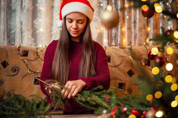 Portret van een vrouw met een rode kerstmuts die op de bank zit en een kerstkrans maakt