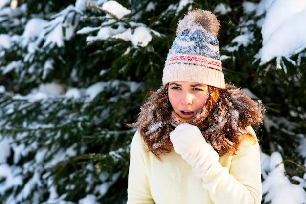 Portret van een vrouw met een sjaal en een hoed, de vrouw verstijfde in de winter, hoest vanwege een verkoudheid. kopieer de ruimte