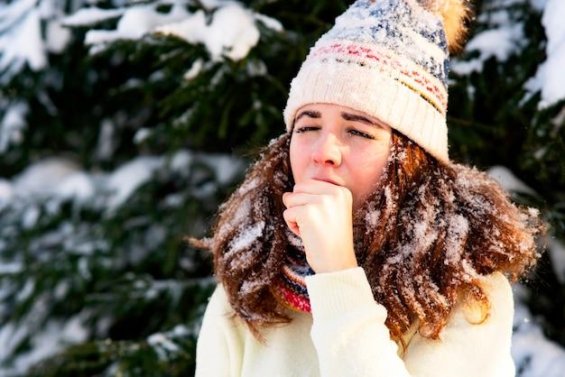 Portret van een vrouw met een sjaal en een hoed, de vrouw verstijfde in de winter, hoest vanwege een verkoudheid.