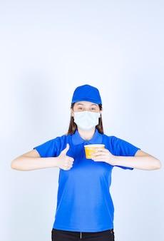 Portret van een vrouw met een uniform en medisch masker met een plastic beker die duim omhoog laat zien