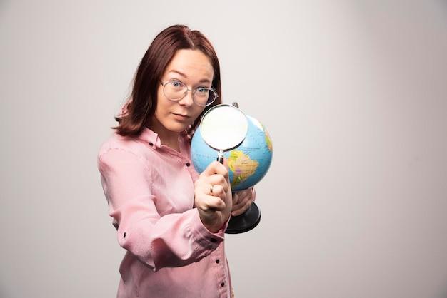 Portret van een vrouw met een vergrootglas en earth globe. hoge kwaliteit foto