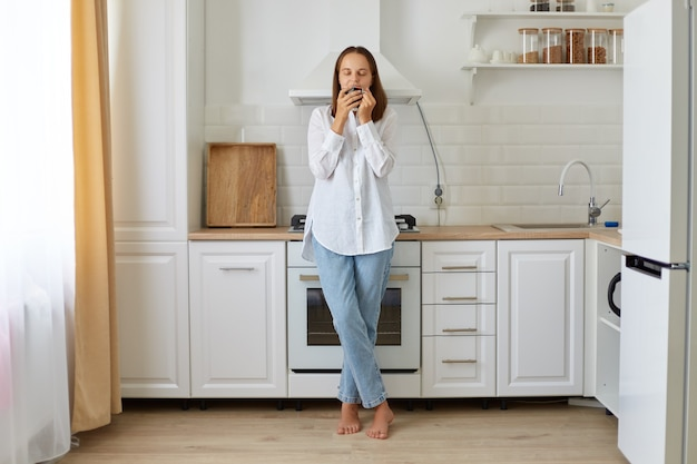 Portret van een vrouw met een wit overhemd en een spijkerbroek die in haar keuken een kopje koffie ruikt en 's ochtends een aromadrankje ruikt terwijl ze in de keuken poseert.