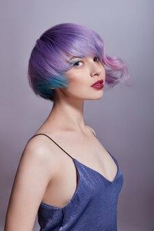 Portret van een vrouw met felgekleurd vliegend haar, alle tinten paars. haarkleuring, mooie lippen en make-up. haren wapperen in de wind. sexy meisje met kort haar. professionele kleuring