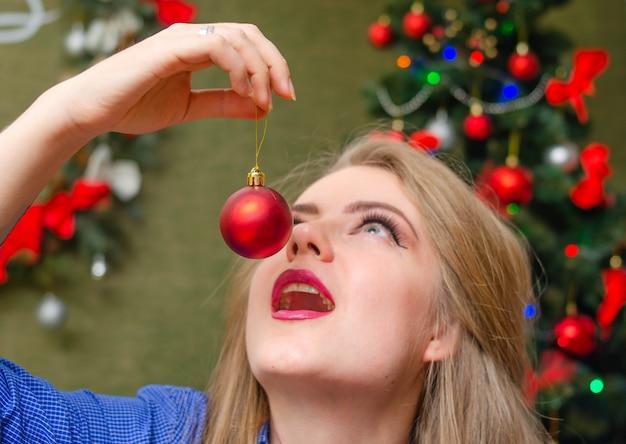 Portret van een vrouw met felrode lippen, blond lang haar tegen de nieuwjaarsboom. jonge vrouw in een blauw herenoverhemd. een kerstbalversiering voor zich houden. een bal eten