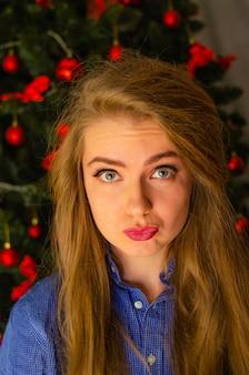 Portret van een vrouw met felrode lippen, blond lang haar tegen de nieuwjaarsboom. jonge vrouw in een blauw herenoverhemd. vakantie. vrolijk kerstfeest. grappig gezicht