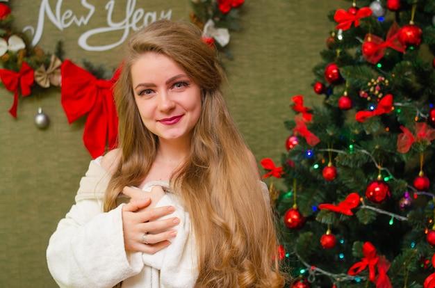 Portret van een vrouw met felrode lippen, blond lang haar tegen de nieuwjaarsboom. jonge vrouw in een witte warme jas, schouders zijn zichtbaar. vakantie. vrolijk kerstfeest
