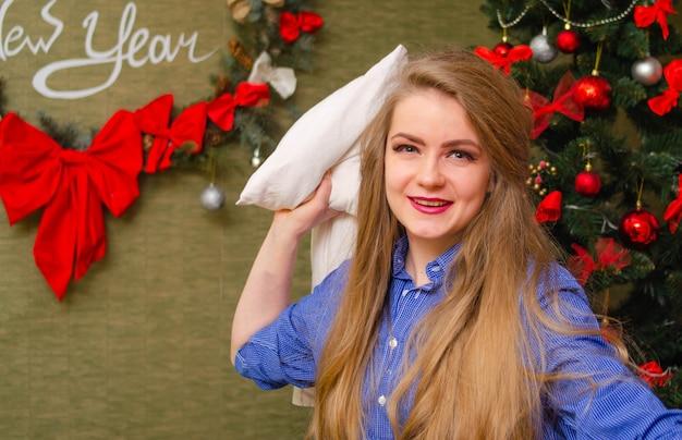 Portret van een vrouw met felrode lippen, blond lang haar tegen de nieuwjaarsboom. jonge vrouw met een wit kussen in zijn handen