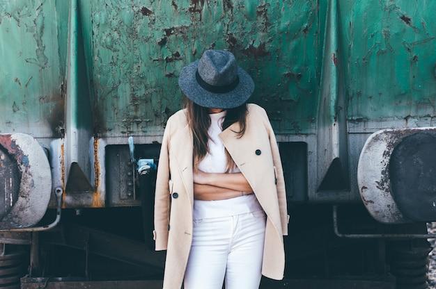 Portret van een vrouw met gekruiste armen die een hoed en een beige jas dragen die tegen een verlaten treinwagon leunt.
