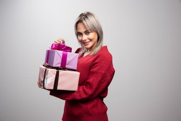 Portret van een vrouw met geschenkdozen op een grijze achtergrond.