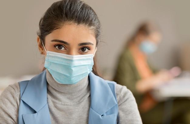Portret van een vrouw met gezichtsmasker op kantoor