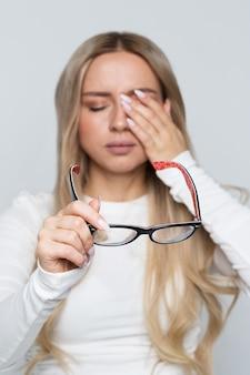 Portret van een vrouw met haar bril terwijl ze haar ogen wrijft
