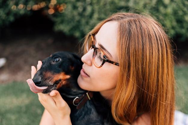 Portret van een vrouw met haar hond tong uitsteekt