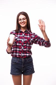 Portret van een vrouw met hallo gebaar drinkt thee of koffie uit papieren beker op wit.