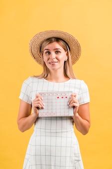 Portret van een vrouw met hoed die haar menstruele kalender houdt