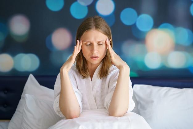 Portret van een vrouw met hoofdpijn, met haar handen op haar slapen