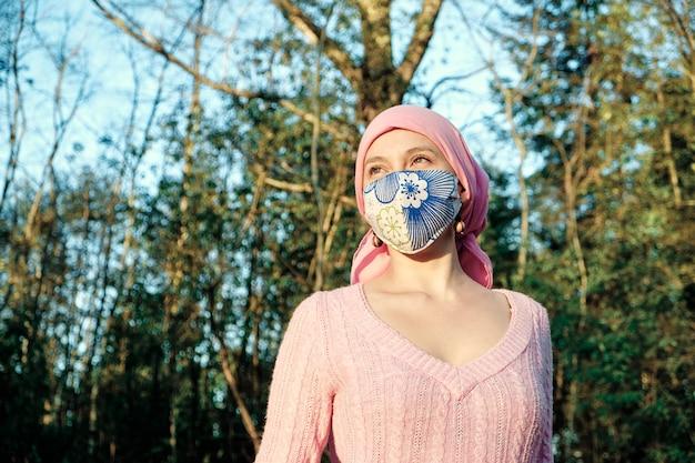 Portret van een vrouw met kanker die een gezichtsmasker draagt om zich buitenshuis te beschermen
