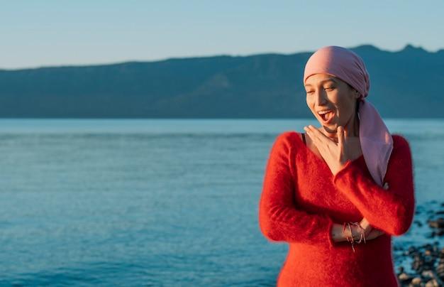 Portret van een vrouw met kanker die in gelukkige schok het water bekijkt