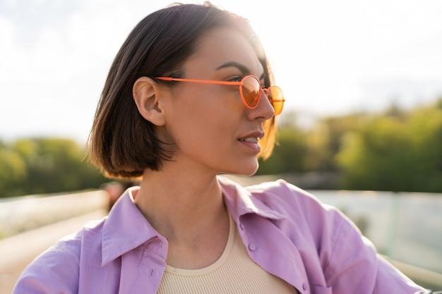 Portret van een vrouw met kort haar in stijlvolle zomeruitrusting, drink koffie op de moderne brug close-up