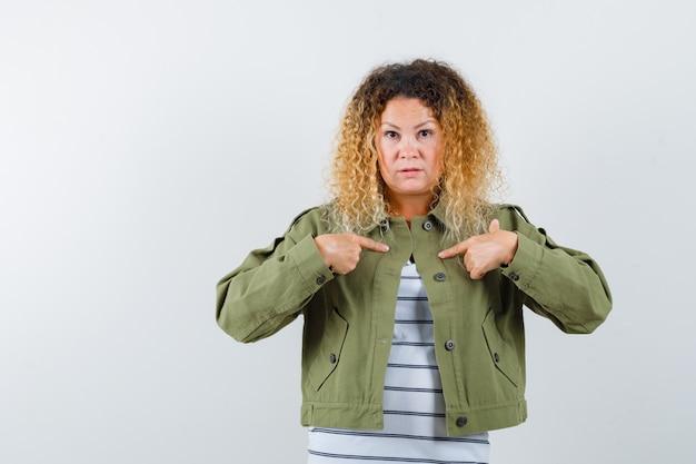 Portret van een vrouw met krullend blond haar wijzend naar zichzelf in groene jas en op zoek perplex vooraanzicht