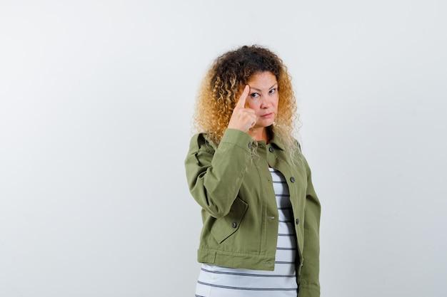 Portret van een vrouw met krullend blond haar wijzend op haar hoofd in een groene jas en op zoek naar intelligent vooraanzicht