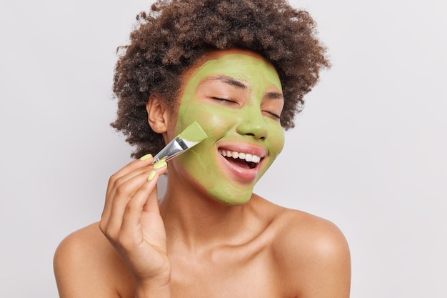 Portret van een vrouw met krullend haar past een groen voedend masker toe met een cosmetische borstel