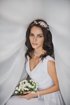 Portret van een vrouw met make-up en een mooi kapsel met bloemen