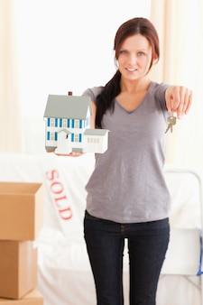 Portret van een vrouw met model huis en sleutels