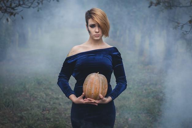Portret van een vrouw met pompoen tussen de bomen in de mist
