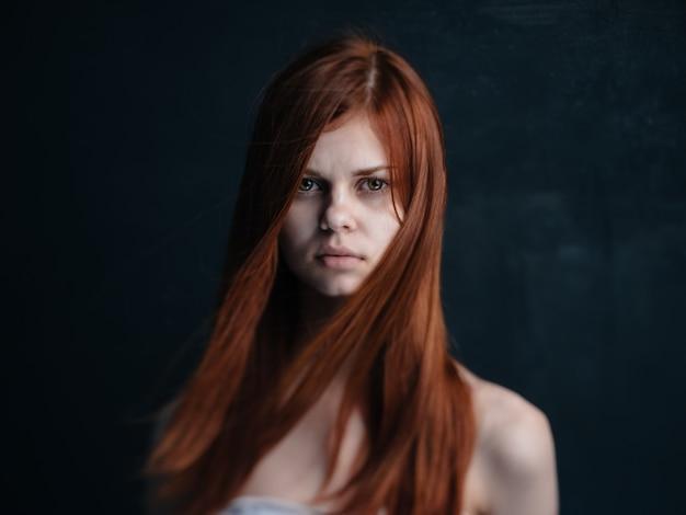 Portret van een vrouw met rood haar op een zwart naakte schoudersmodel als achtergrond