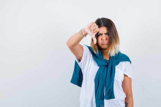 Portret van een vrouw met vastgebonden trui met duim naar beneden, gebogen onderlip in wit t-shirt en teleurgesteld vooraanzicht