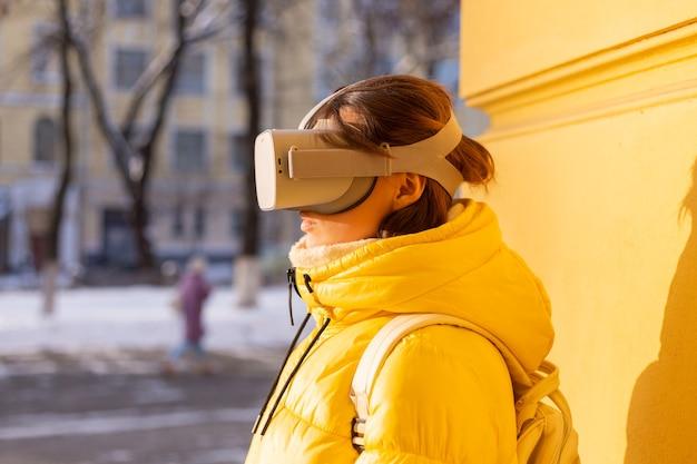 Portret van een vrouw met vr-bril op straat tegen een gele muur in fel zonlicht in de winter in warme kleren