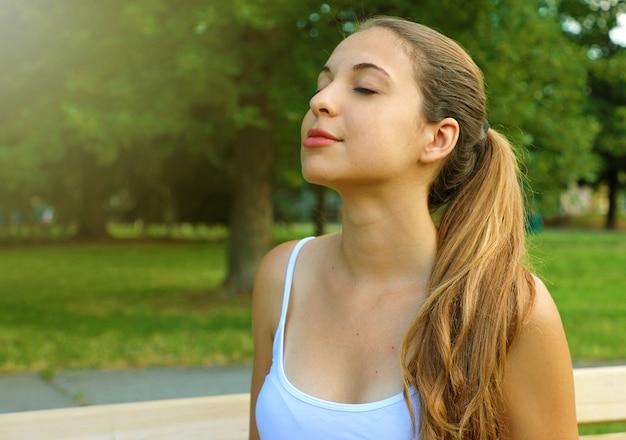 Portret van een vrouw ontspannende ademhaling frisse lucht in het park.