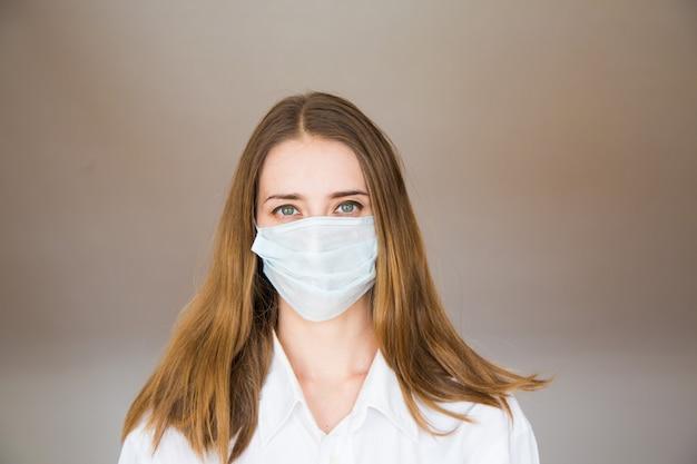 Portret van een vrouw op beige, die een medisch masker draagt. demonstratie van medische apparatuur.
