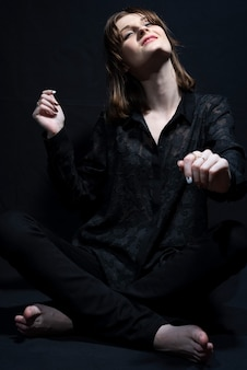 Portret van een vrouw op blote voeten zittend op de vloer en zwaaiend met haar armen dansend op zwarte achtergrond