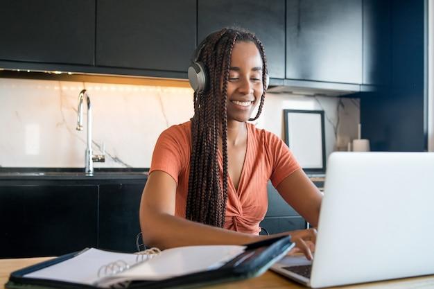 Portret van een vrouw tijdens een videogesprek met laptop terwijl ze vanuit huis werkt.