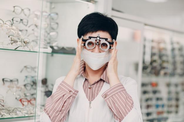 Portret van een vrouw van de optometrist oftalmoloog van middelbare leeftijd die beschermend medisch gezichtsmasker draagt