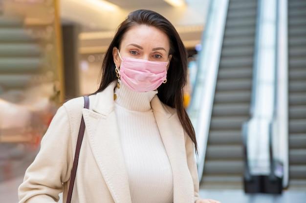 Portret van een vrouw van middelbare leeftijd met een beschermend masker op de achtergrond van een roltrap in de openbare ruimte