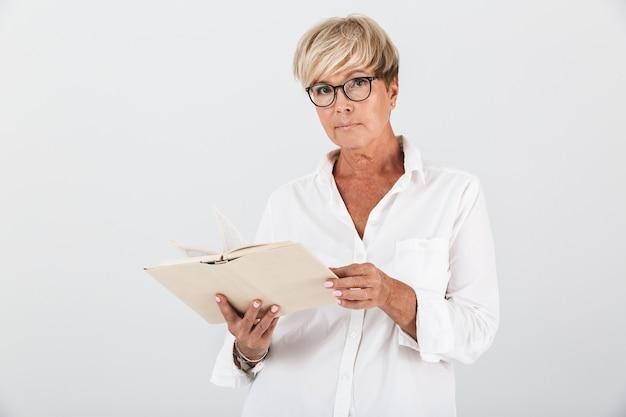 Portret van een vrouw van middelbare leeftijd met een bril die een boek vasthoudt en naar een camera kijkt die over een witte muur in de studio is geïsoleerd;