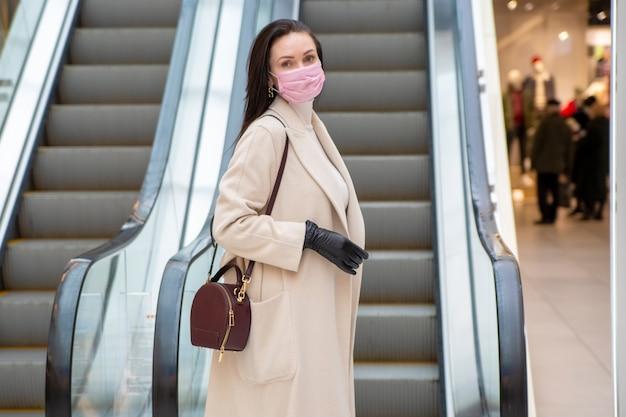 Portret van een vrouw van middelbare leeftijd met handschoenen en masker op roltrap in openbare ruimte