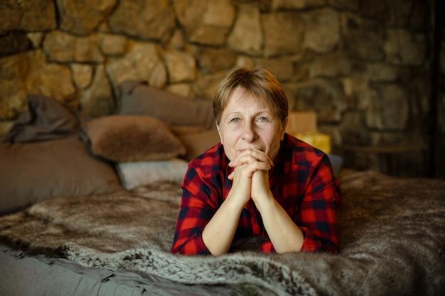 Portret van een vrouw van pensioengerechtigde leeftijd in het huis.