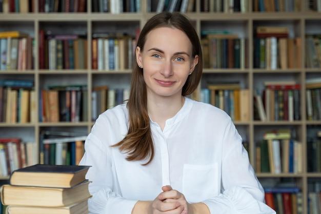 Portret van een vrouw zittend aan een tafel in de bibliotheek naast een boekenplank praten uit te leggen