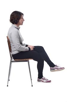 Portret van een vrouw zittend op een stoel op een witte achtergrond, kijkend naar de zijkant en benen gekruist