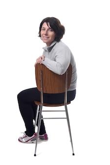 Portret van een vrouw zittend op een stoel op een witte achtergrond