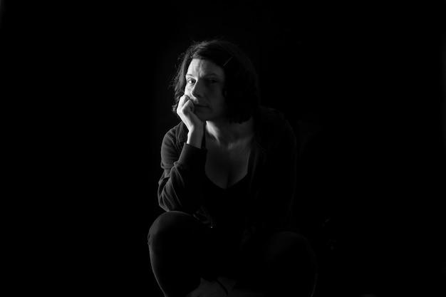 Portret van een vrouw zittend op zwarte achtergrond