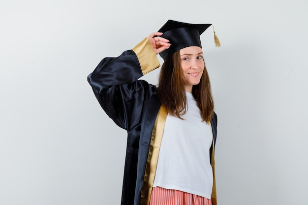 Portret van een vrouwelijke afgestudeerde die groetgebaar in uniforme, vrijetijdskleding toont en zelfverzekerd vooraanzicht kijkt