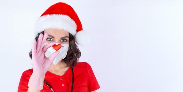 Portret van een vrouwelijke arts in een medisch masker kerst man hoed handschoenen met de afbeelding van een hart een symbool van liefde een gezond hart