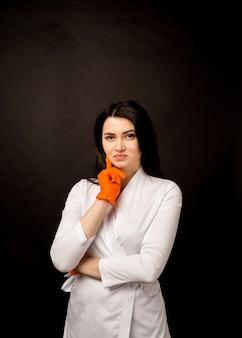Portret van een vrouwelijke arts in een wit uniform en oranje handschoenen op zwart