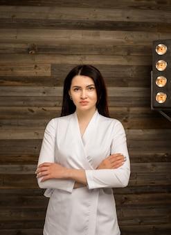 Portret van een vrouwelijke arts in een wit uniform staat op houten muur